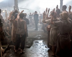 The citizens of District 8 salute Katniss.
